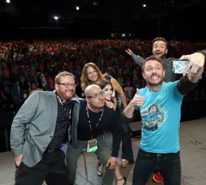 TROLLS filmakers and voice actors take a selfie with the audience at DreamWorks Animation's Comic Con Hall H Panel. (from left) Co-Director Walt Dorn, Director Mike Mitchell, Anna Kendrick, Producer Gina Shay, Moderator Chris Hardwick, and Justin Timberlake.