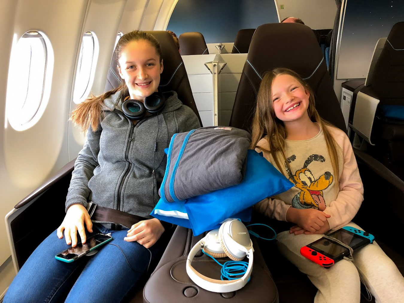 Two girls sitting in first class airplane seats