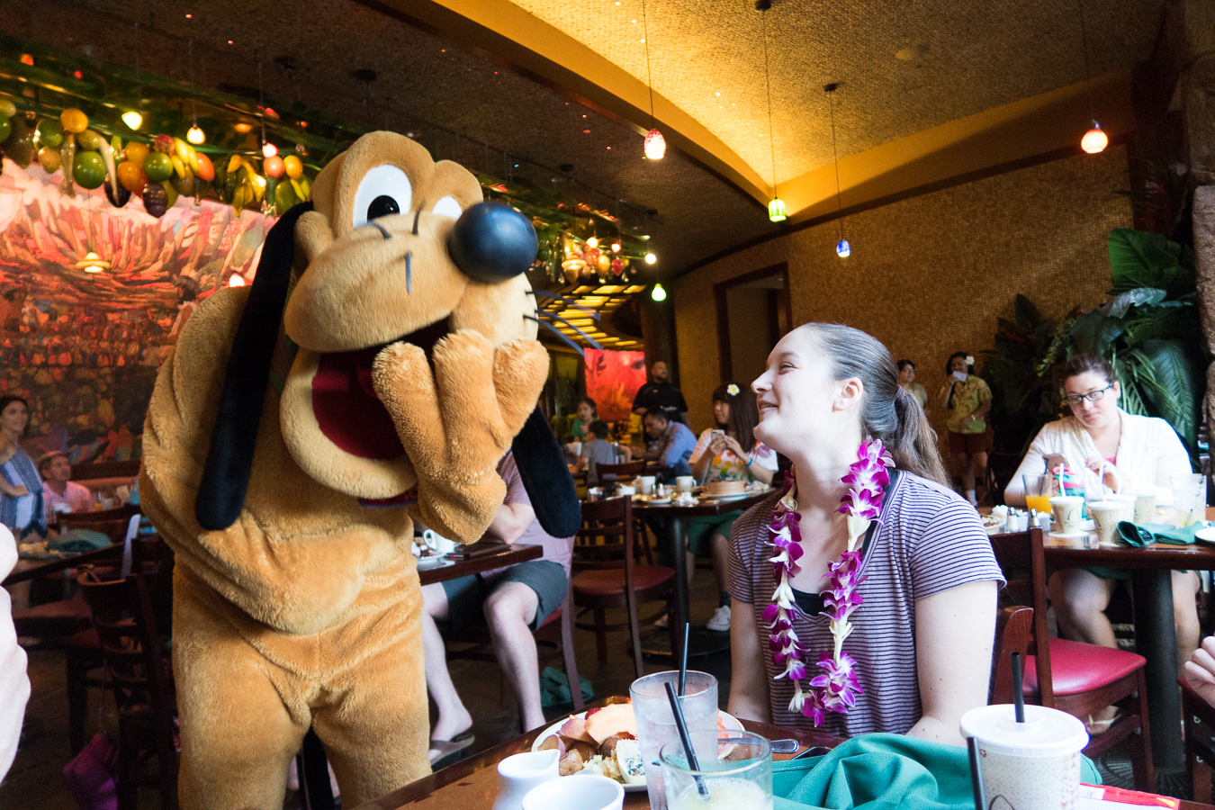 Girl laughing with Pluto at the breakfast buffet at Disney's Aulani