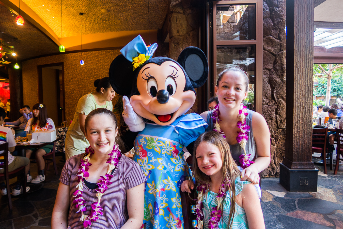 Three girls posing with Minnie Mouse at the breakfast buffet at Disney's Aulani
