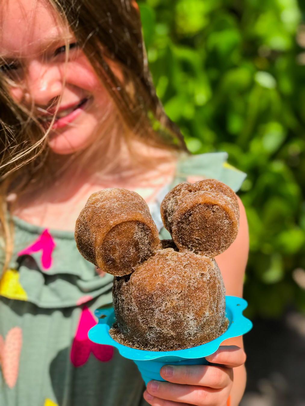 Girl holding root beer flavored Mickey Mouse-shaped Shave Ice at Disney's Aulani