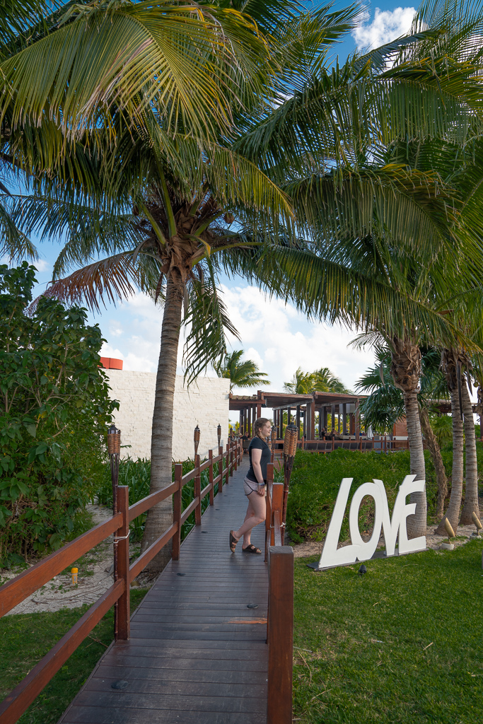 Palm tree-lined walkway leading to a restaurant at the Grand at Moon Palace Cancun