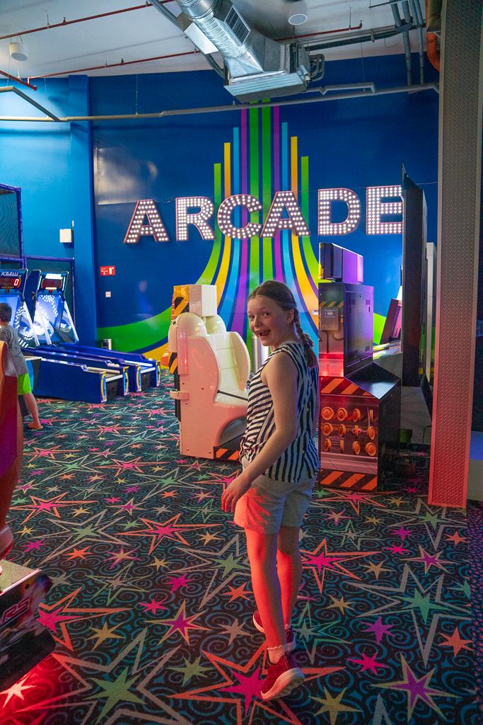 Girl enjoying the arcade in the Playroom at the Grand at Moon Palace Cancun
