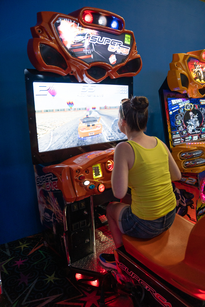 Girl playing a driving simulation game in the teen club at the Grand at Moon Palace Cancun