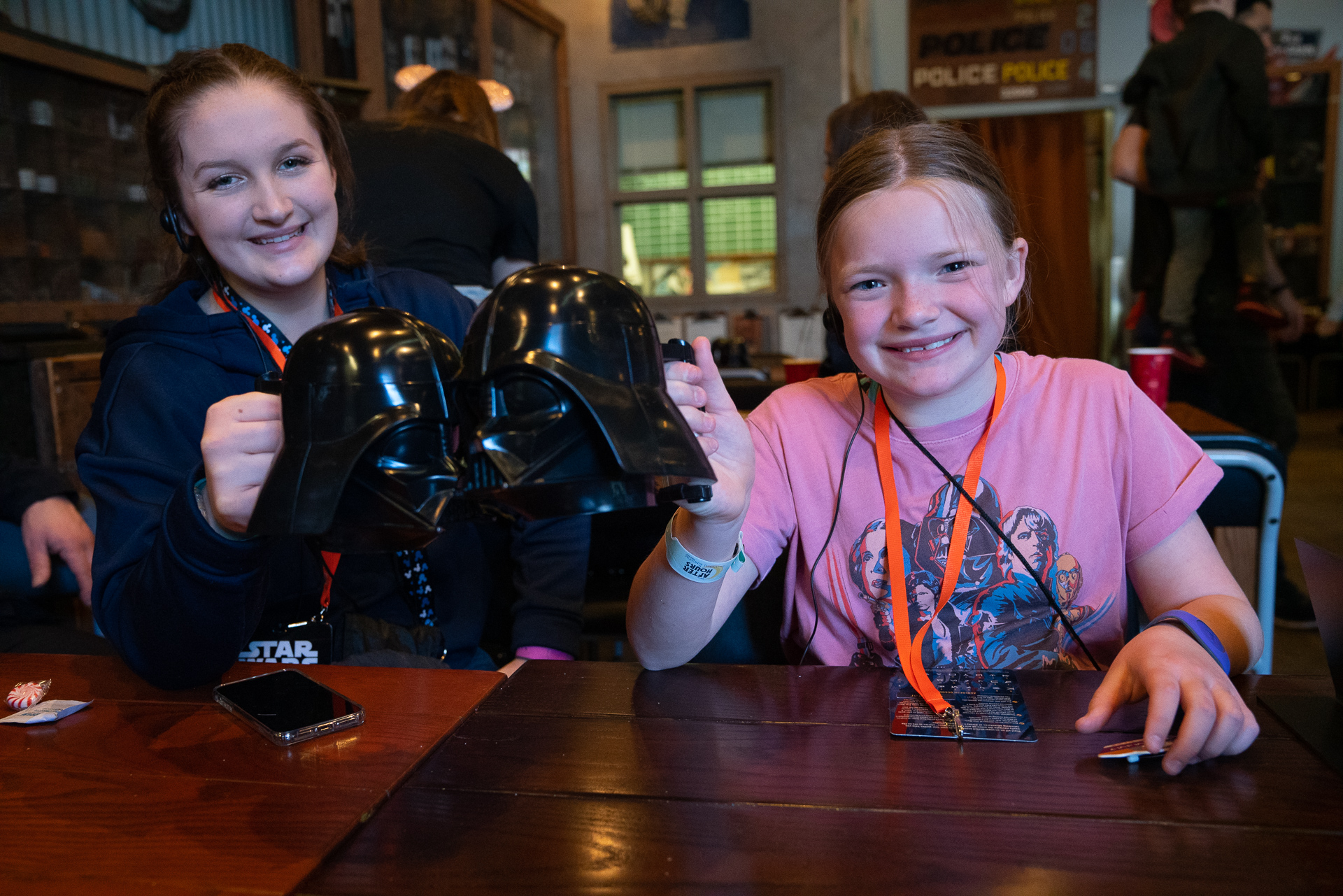 Two girls posing with the souvenir Darth Vader mugs that come with the VIP Star Wars tour at Disney's Hollywood Studios at Walt Disney World