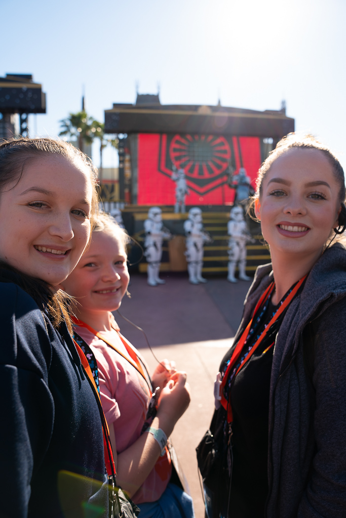Three girls posing in front of a First Order presentation during a VIP Star Wars tour at Disney's Hollywood Studios at Walt Disney World