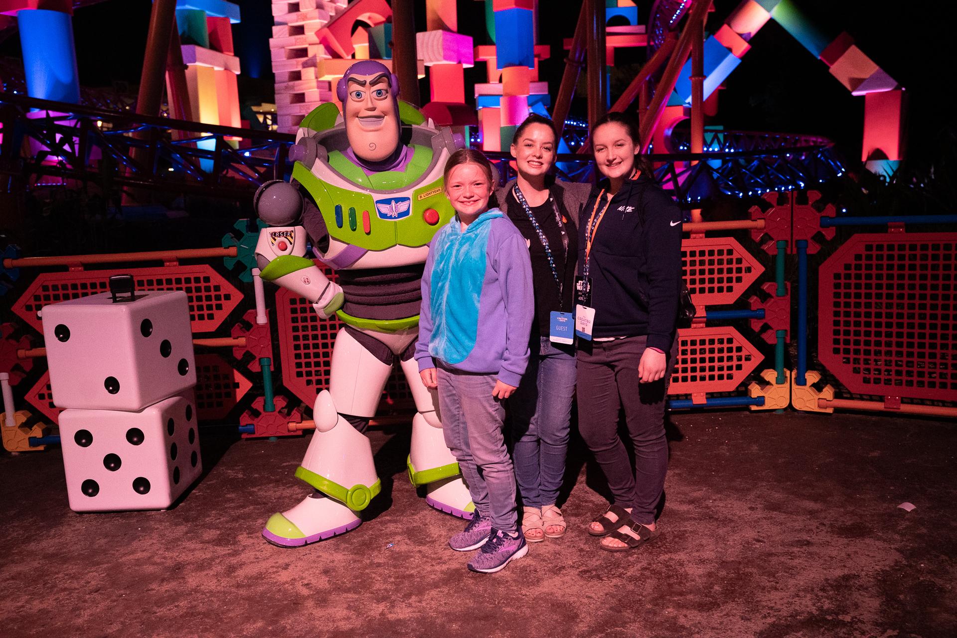 Three girls posing with Buzz Lightyear in Toy Story Land at Disney's Hollywood Studios at Walt Disney World