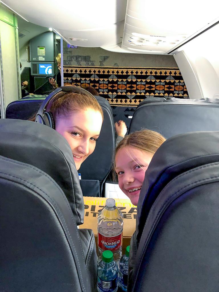 Two girls sitting in first class on a flight to Walt Disney World