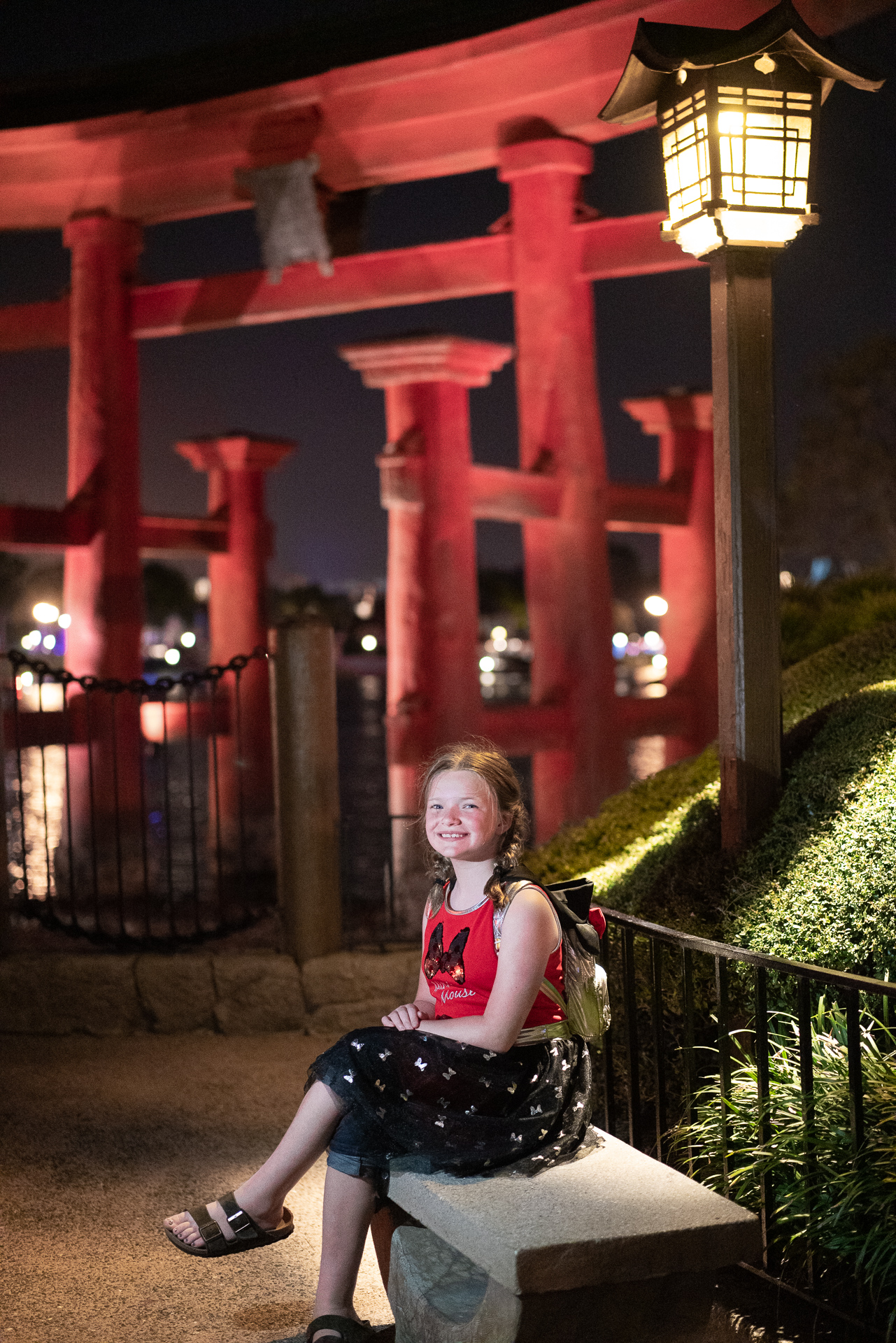 Girl sitting on a bench as Epcot closes for the night at Walt Disney World
