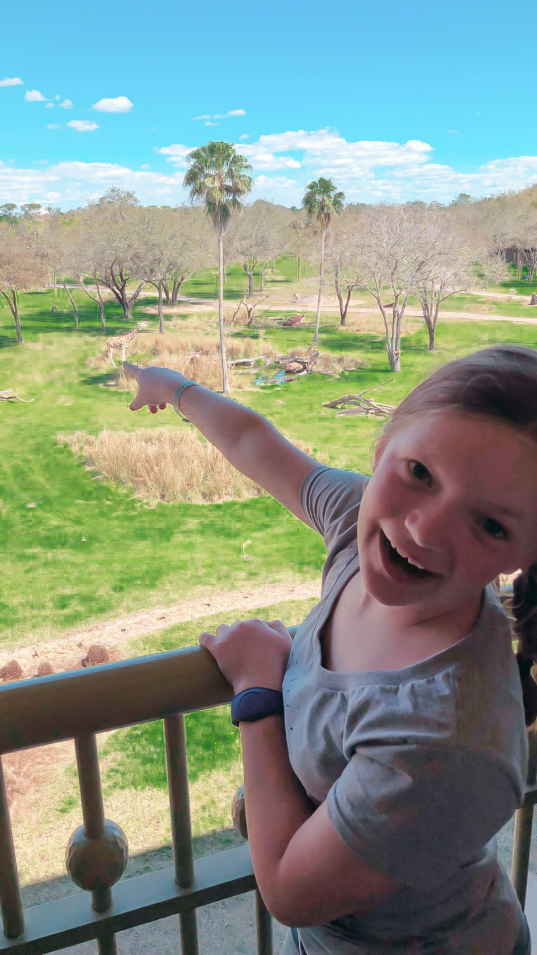 Girl on the balcony pointing at a giraffe at the Animal Kingdom Lodge at Walt Disney World