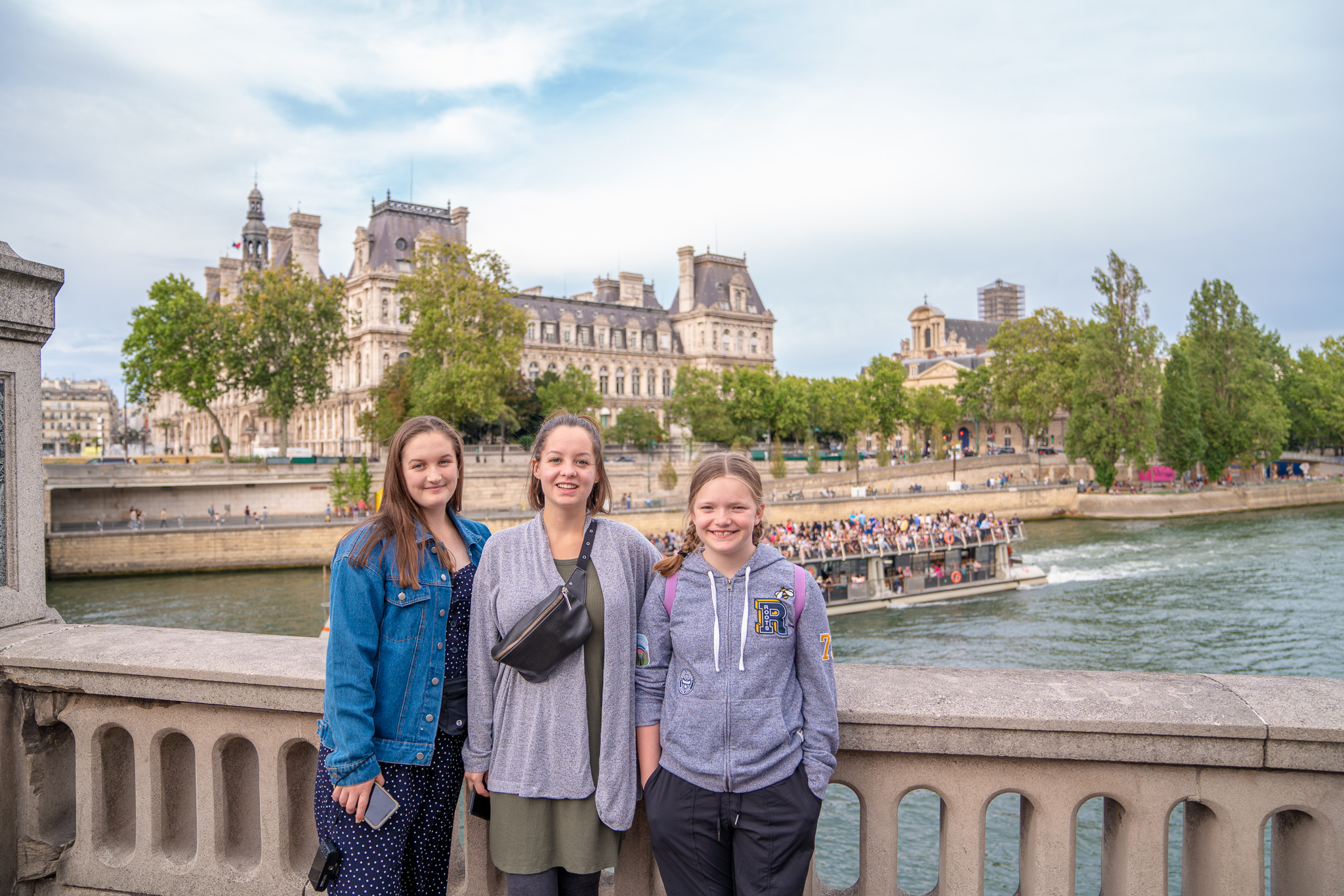 Three girls standing on a bridge over the Seine river in Paris, France