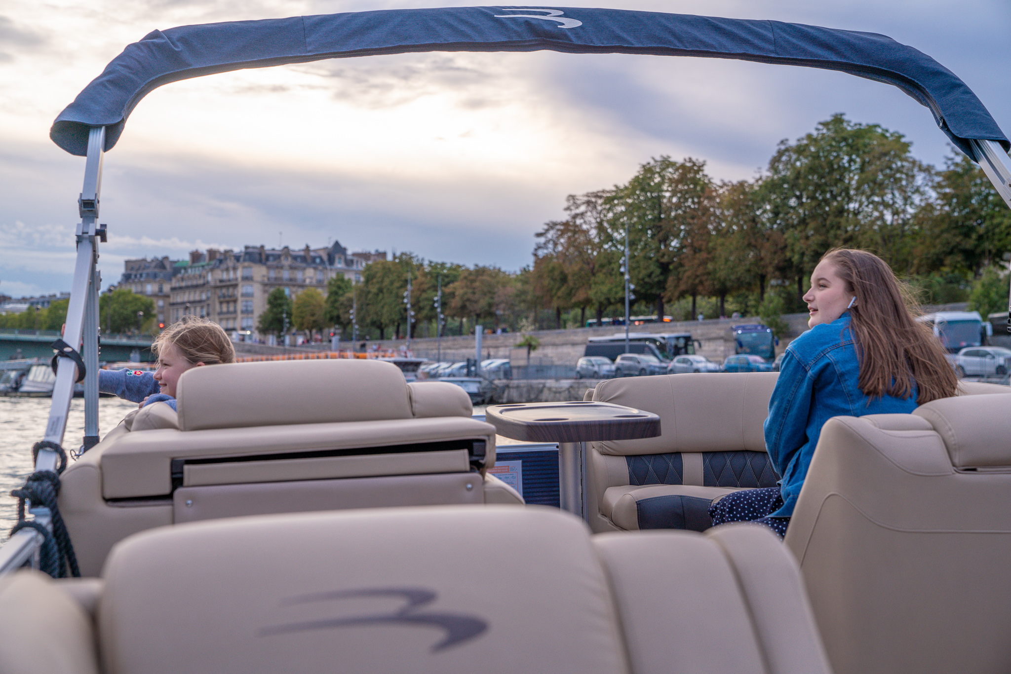 Two girls sitting in a private boat on the Seine river in Paris, France