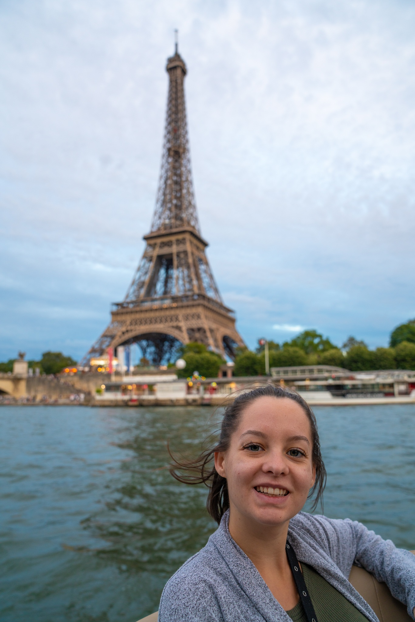 Teen girl in front of the Eiffel Tower on the Seine river in Paris, France