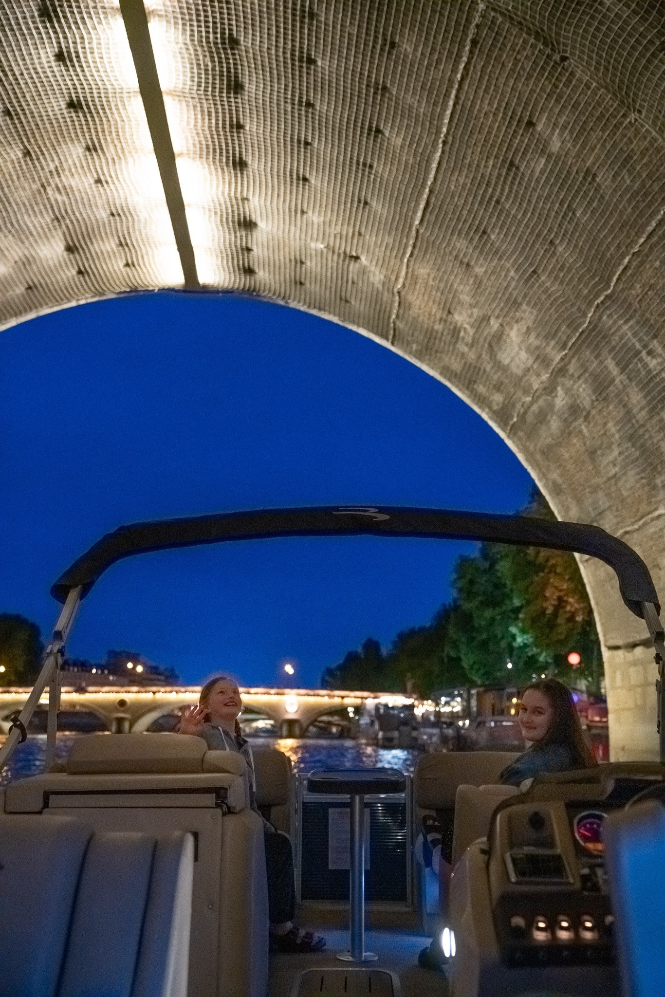 Two girls in a private boat passing under a bridge across the Seine river at twilight in Paris, France